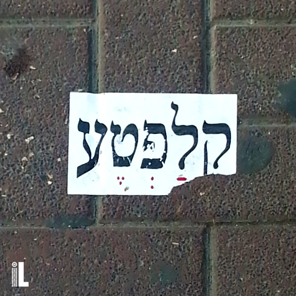 Klafte sticker, peeling off the Ackerstein pavement in Israel.