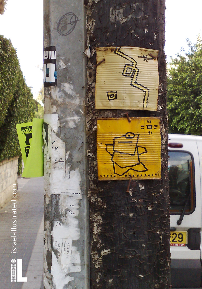 Kufsonim characters drawn on what looks like a hammered tin can, and nailed to a lamp post in the center of Tel Aviv.